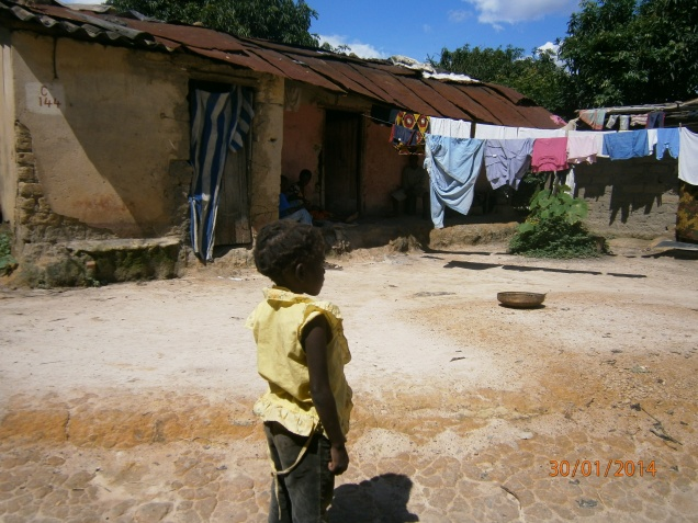 African child in yellow top standing in front of house with corrugated iron roof and washing line