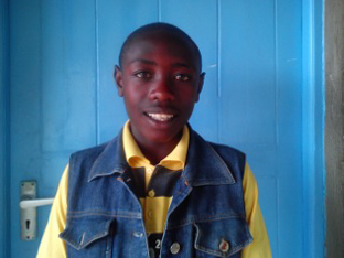 Kenyan Boy from Naivasha Children's Shelter, blue denim waste coat, yellow and blue football shirt, blue door