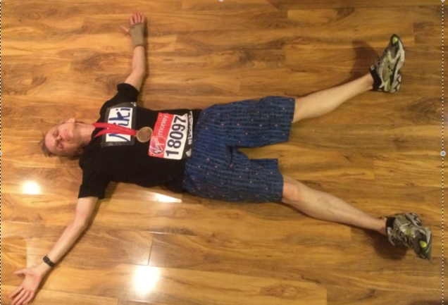 Woman lying on floor wearing shirt,  tee shirt, running shoes and London Marathon number