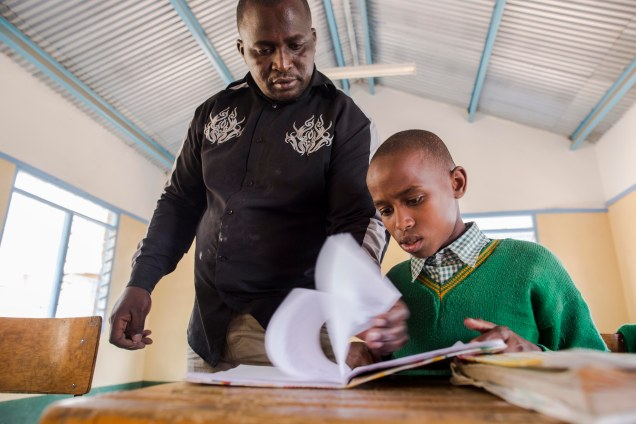 African boy in green jersey leafs through book while overseen by teacher