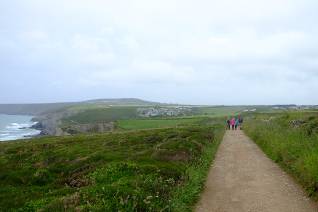 Path, 4 walkers, sea, houses in distance