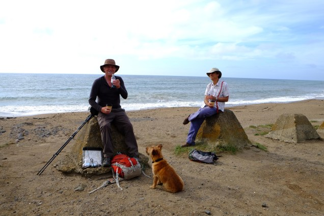 two men sitting on bollards on beach drinking with dog looking on