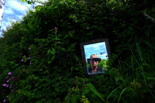 Man's face in mirror in hedge