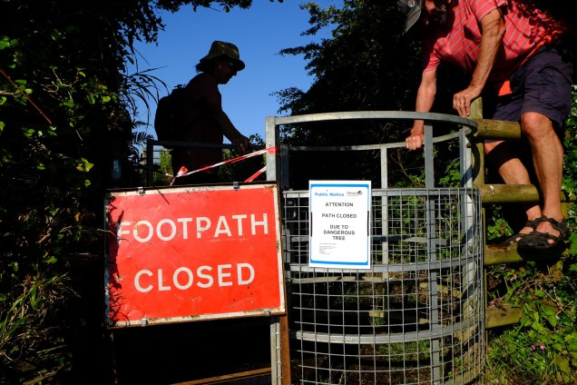 footpath closed sign, man climbing fence