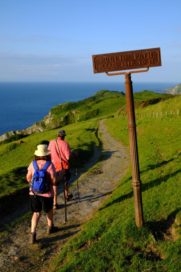 Man and woman on footpath sign keep to the path