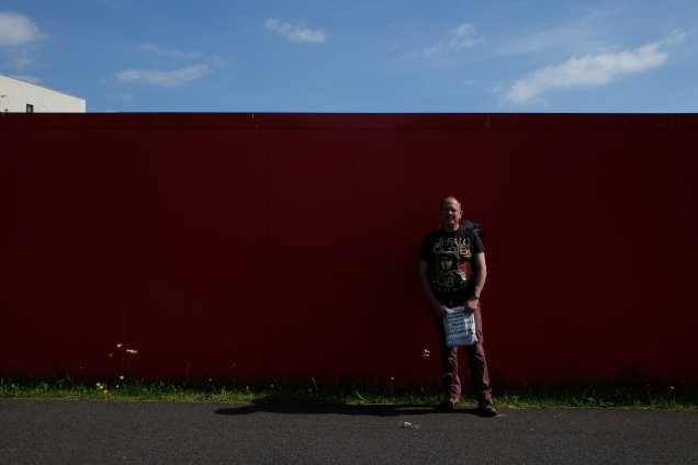 Man standing in front of red wall