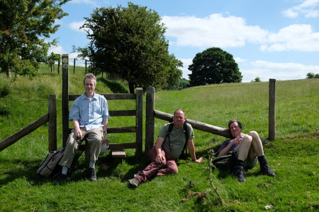 Three men resting by fence