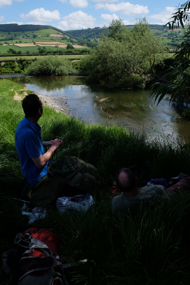 Two walkers picnic on Offa's Dyke by the River Severn