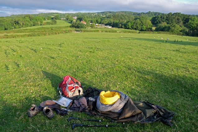Rucksack, shoes, sticks sleeping bag, in foreground, green field, grey sky