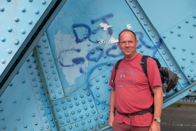 Man in Red Grateful Deat shirt in front of blue metal work, Queensferry Bridge, River Dee