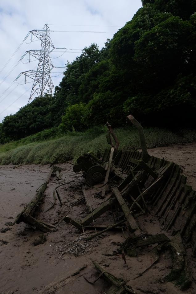 Abandoned boat, beach, woods pylon