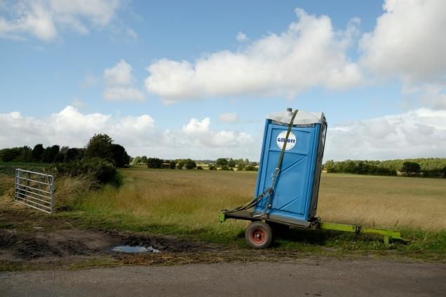 Blue portable lavatory, toilet, w.c. on wheels on edge of road by fields, blue sky, puffy clouds