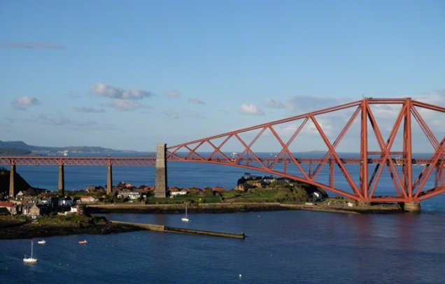 Pink bridge, the Forth Rail Bridge, small houses of North Queensferry below, Blue sky, blue waters of the firth of Forth