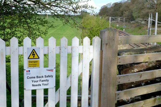 sign on gate by railway track reading 'come back safely your family need you'