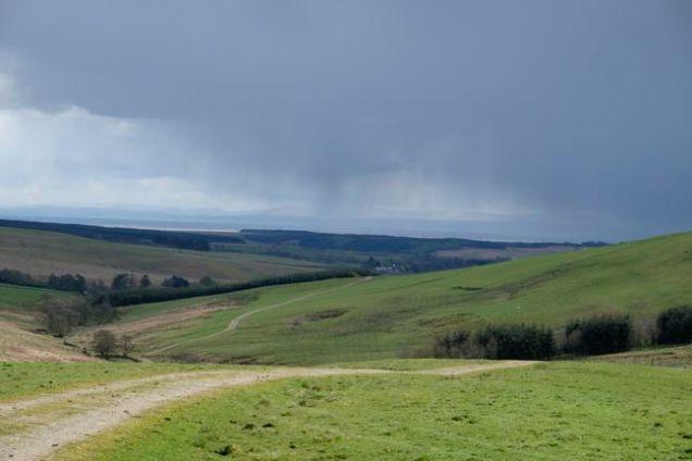 rain in distance above moorland