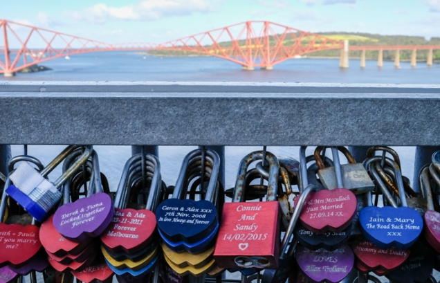 Padlocked hearts, padlocks with names of couples engraved upon them, locked to the Forth Road Bridge with the Forth Rail Bridge in the background