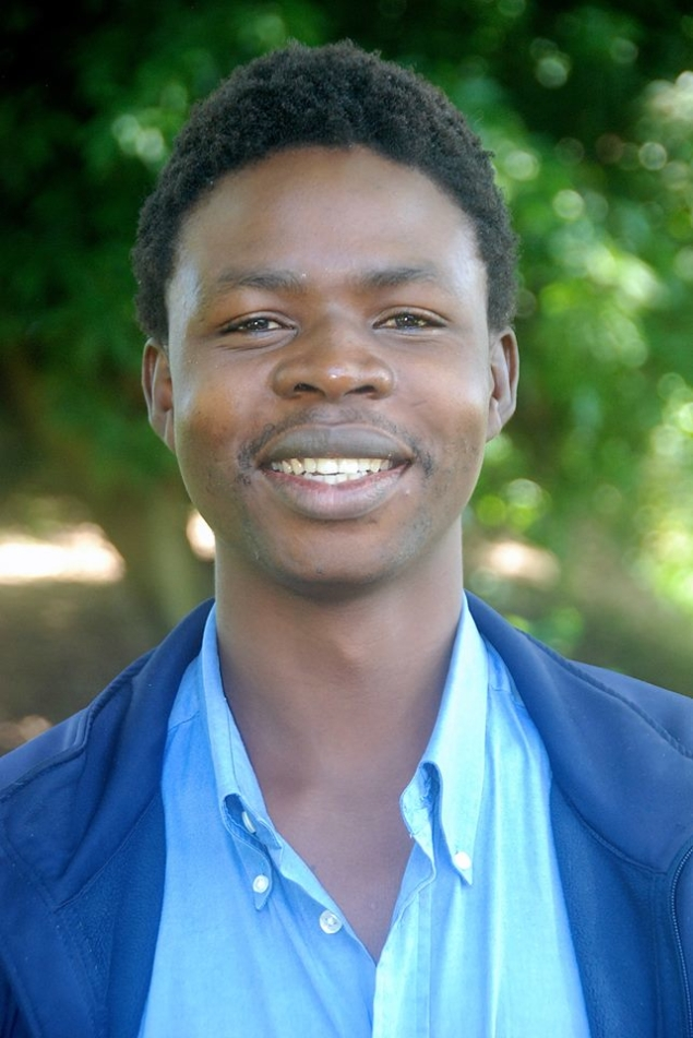 Young African man from Zambia in blue against a green background